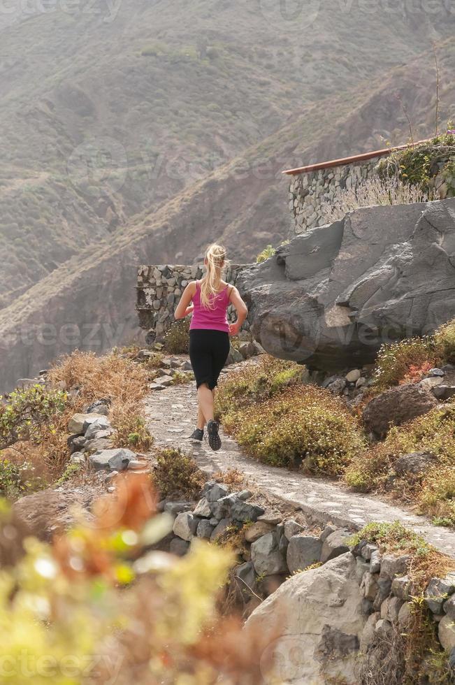 fitness. jonge vrouw die op een bergweg foto
