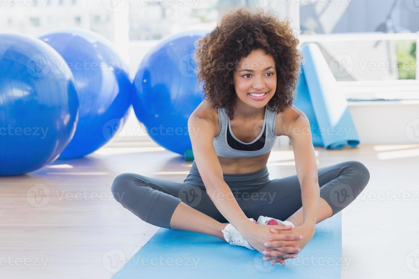 fit vrouw doet de vlinder stretch in de fitnessruimte foto