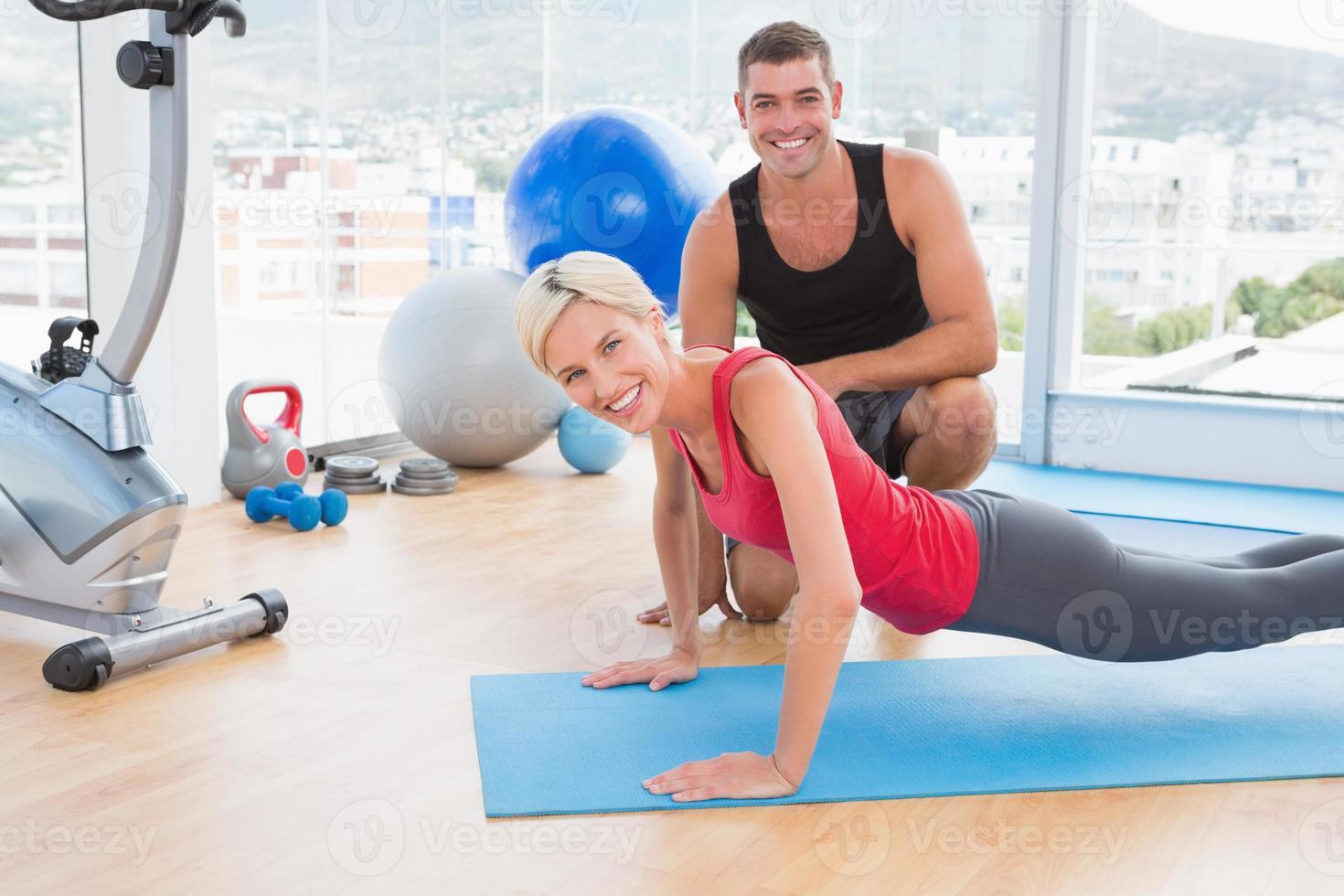 blonde vrouw die aan oefeningsmat werkt met haar trainer foto