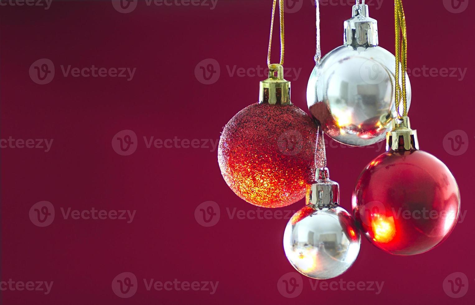 rode en zilveren kerstballen opknoping tegen solide achtergrond foto