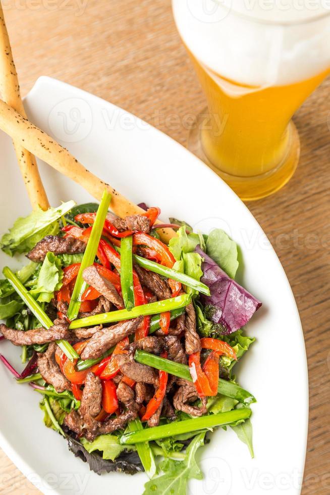plaat van salade van vlees met groenten en lichte beer foto