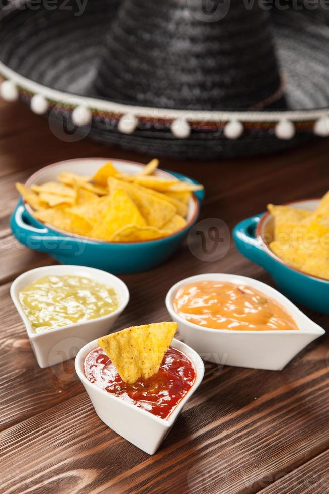 plaat van nacho's met verschillende dips foto
