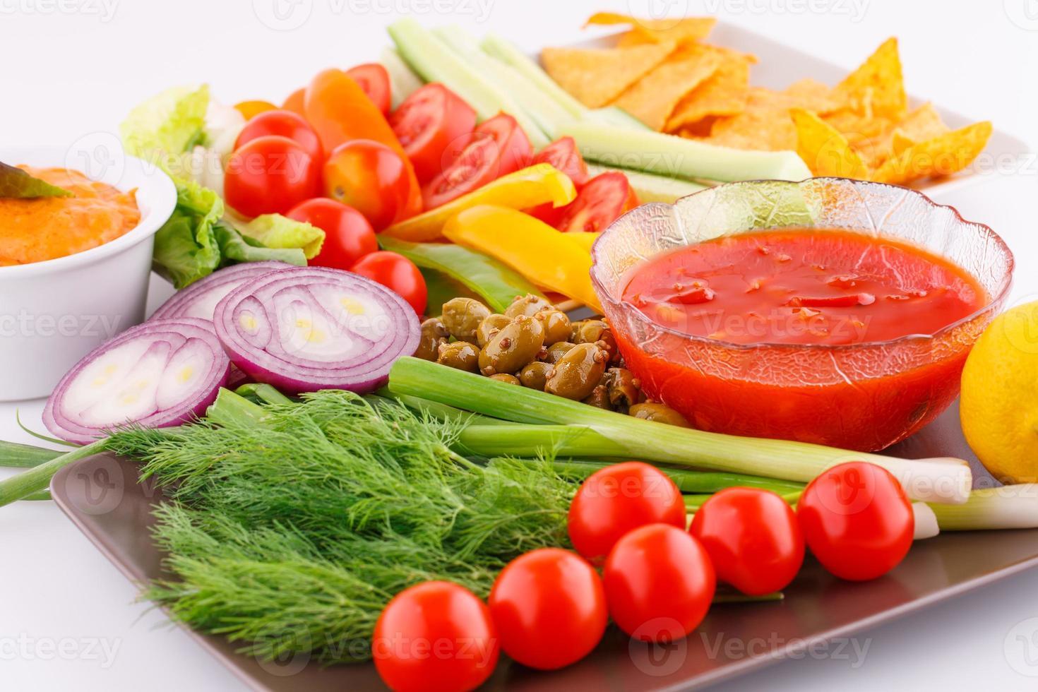 groenten, olijven, nacho's, rode kaas en saus foto