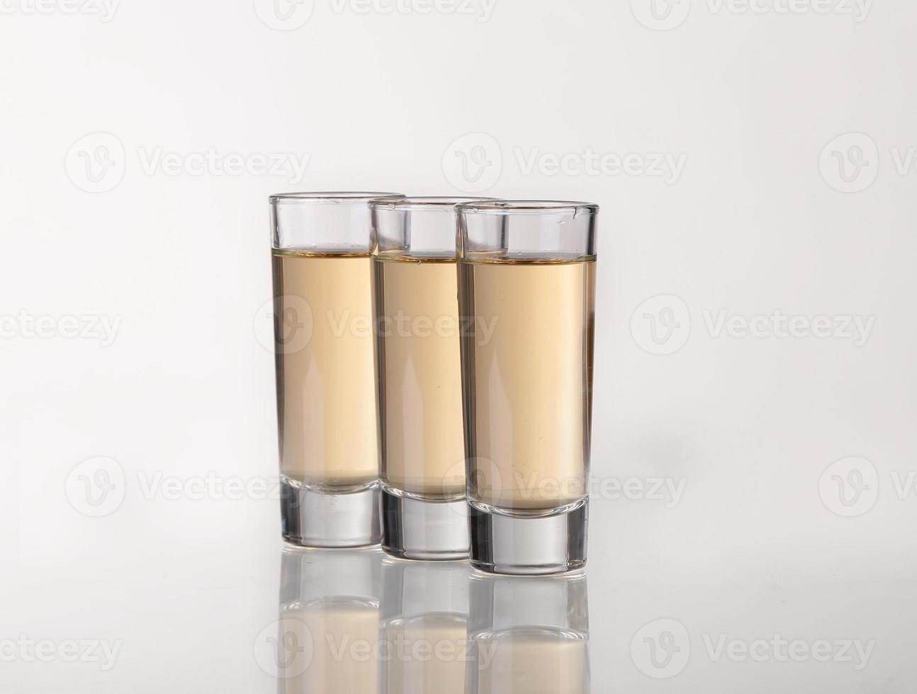 drie gouden tequilaschoten met kalk op witte achtergrond foto