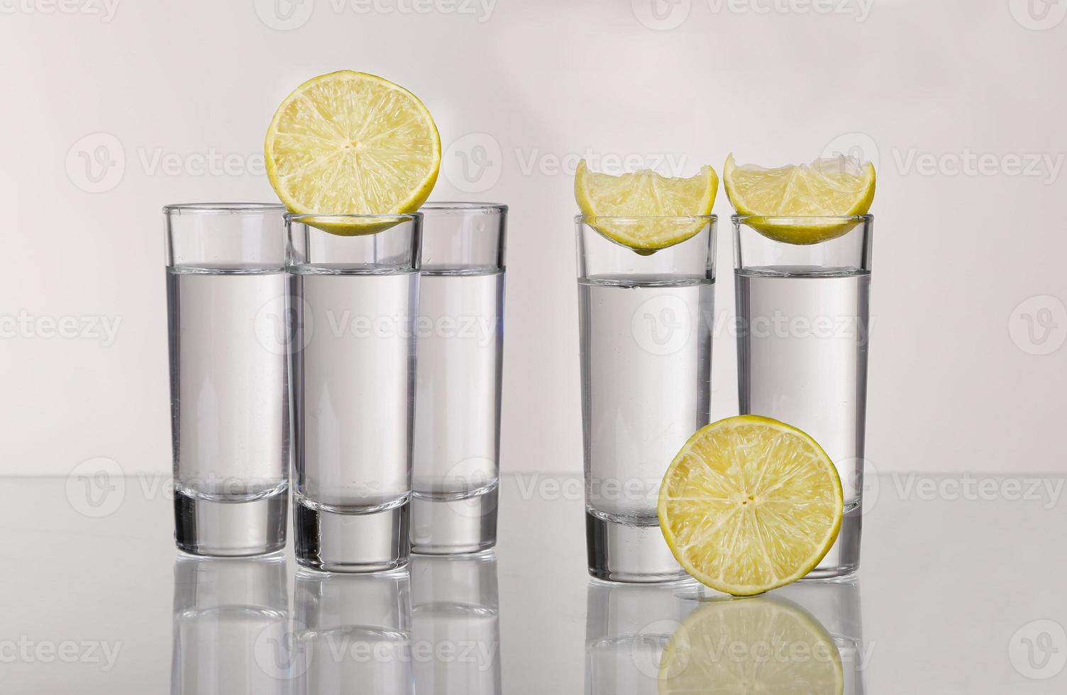 drie gouden tequilaschoten met kalk die op witte achtergrond wordt geïsoleerd foto