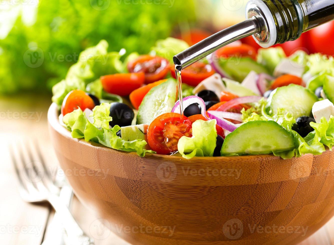 olie gieten in kom groentesalade foto