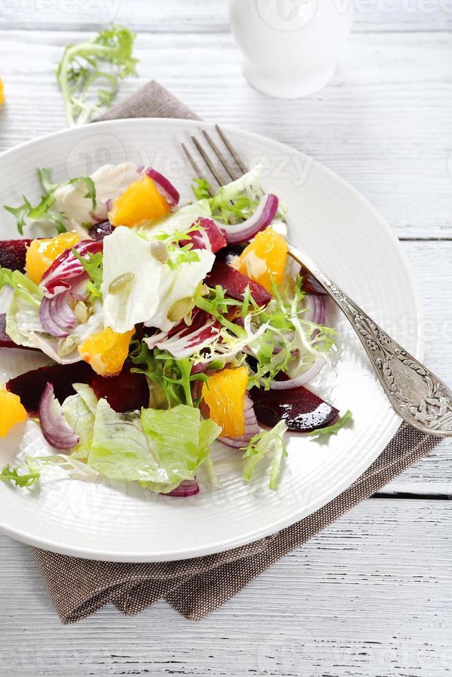 bieten en sinaasappelen in salade op plaat foto