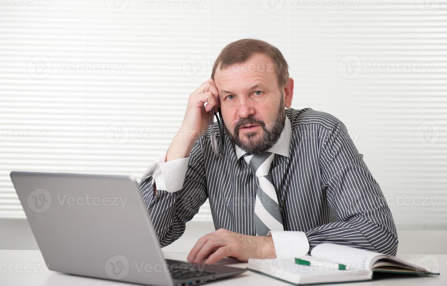 volwassen zakenman die op zijn laptop werkt foto