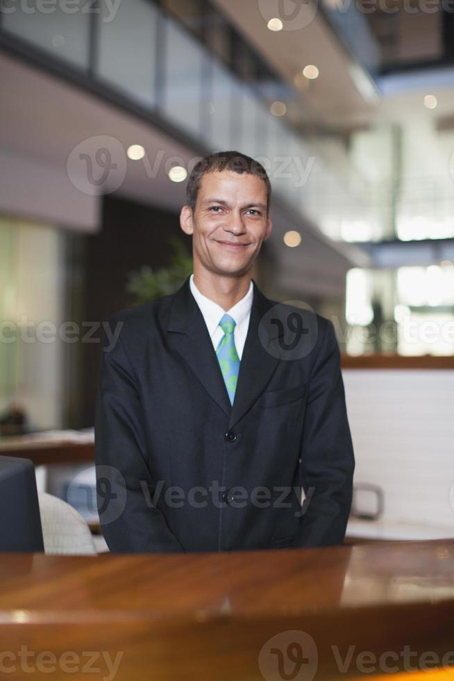 hotel conciërge lachend aan balie foto