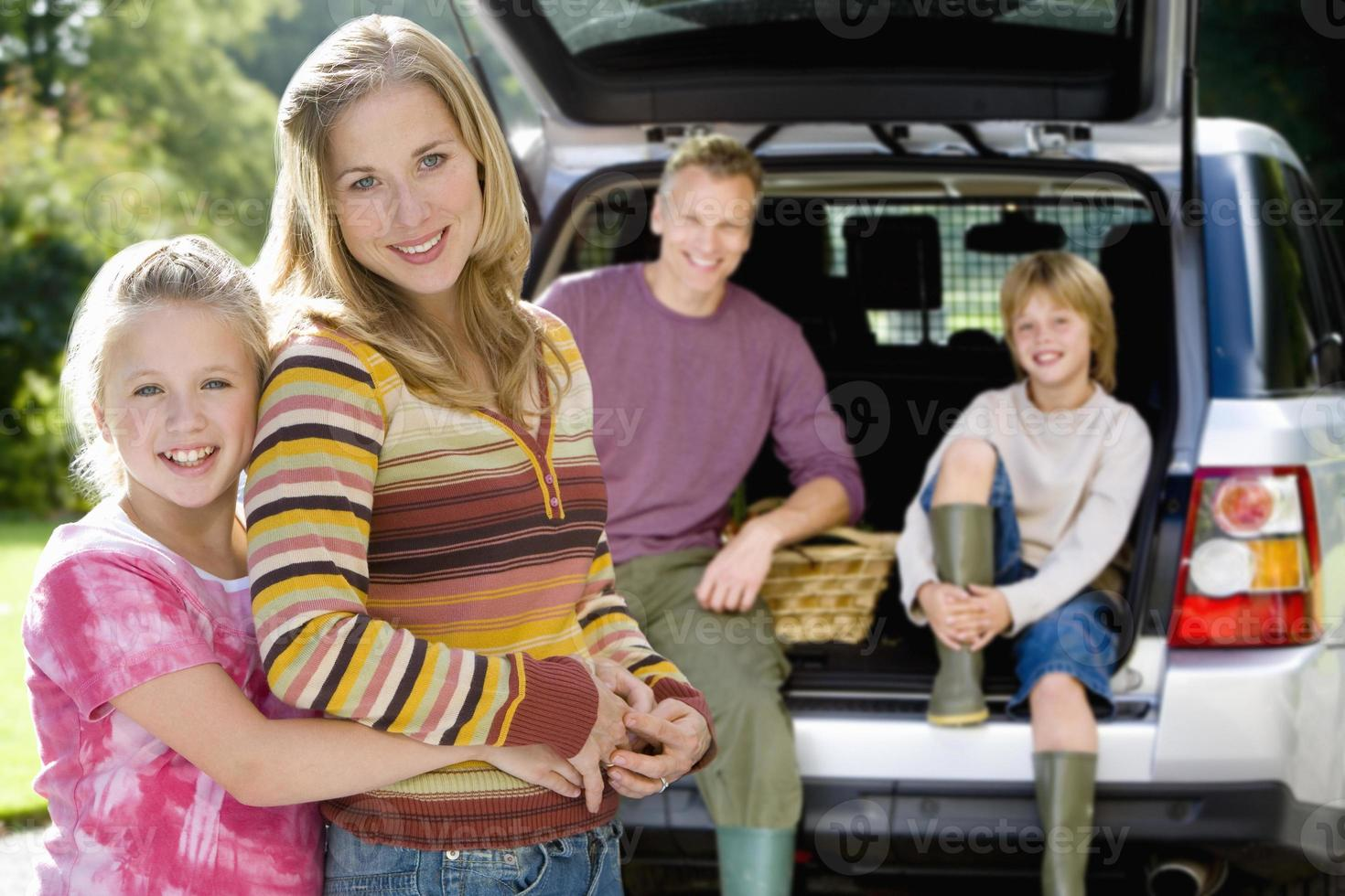 meisje omhelst moeder, vader en zoon (9-11) op de achtergrond, poort foto