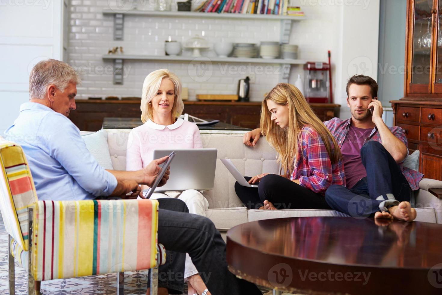 ouders met volwassen nakomelingen die thuis digitale apparaten gebruiken foto