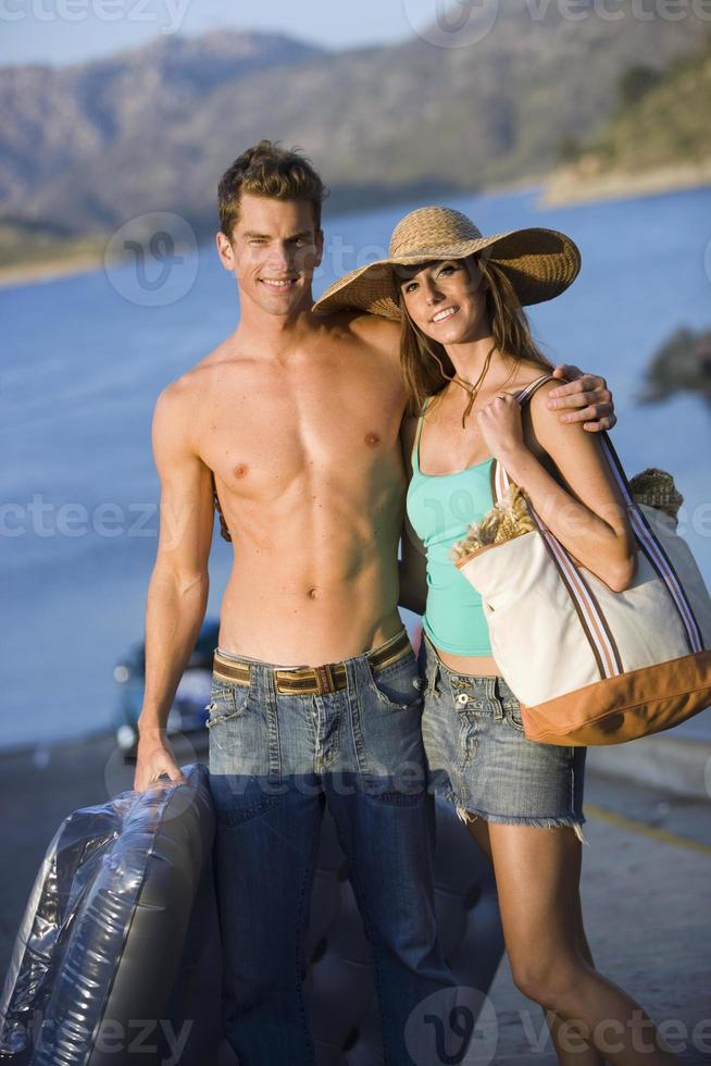 tienerpaar dichtbij meer, jongen die opblaasbaar houdt, meisje dat h draagt foto