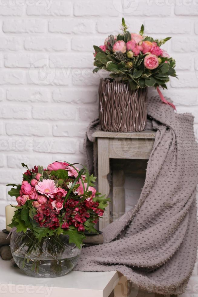 twee boeketten in vazen met pioenen, gerbera, alstroemeria, laat pittosporuma achter foto