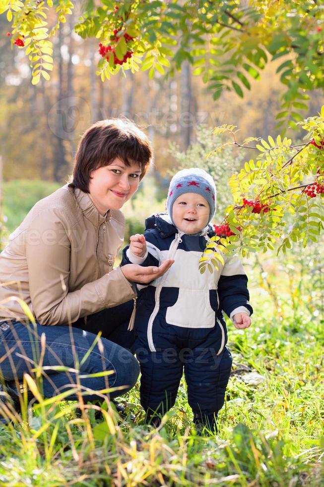 jonge moeder en baby jongen zoon op herfst achtergrond foto