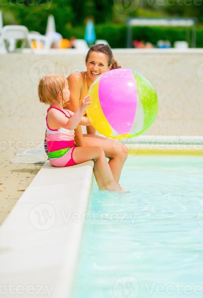 moeder en babymeisje met strandbal bij zwembad foto