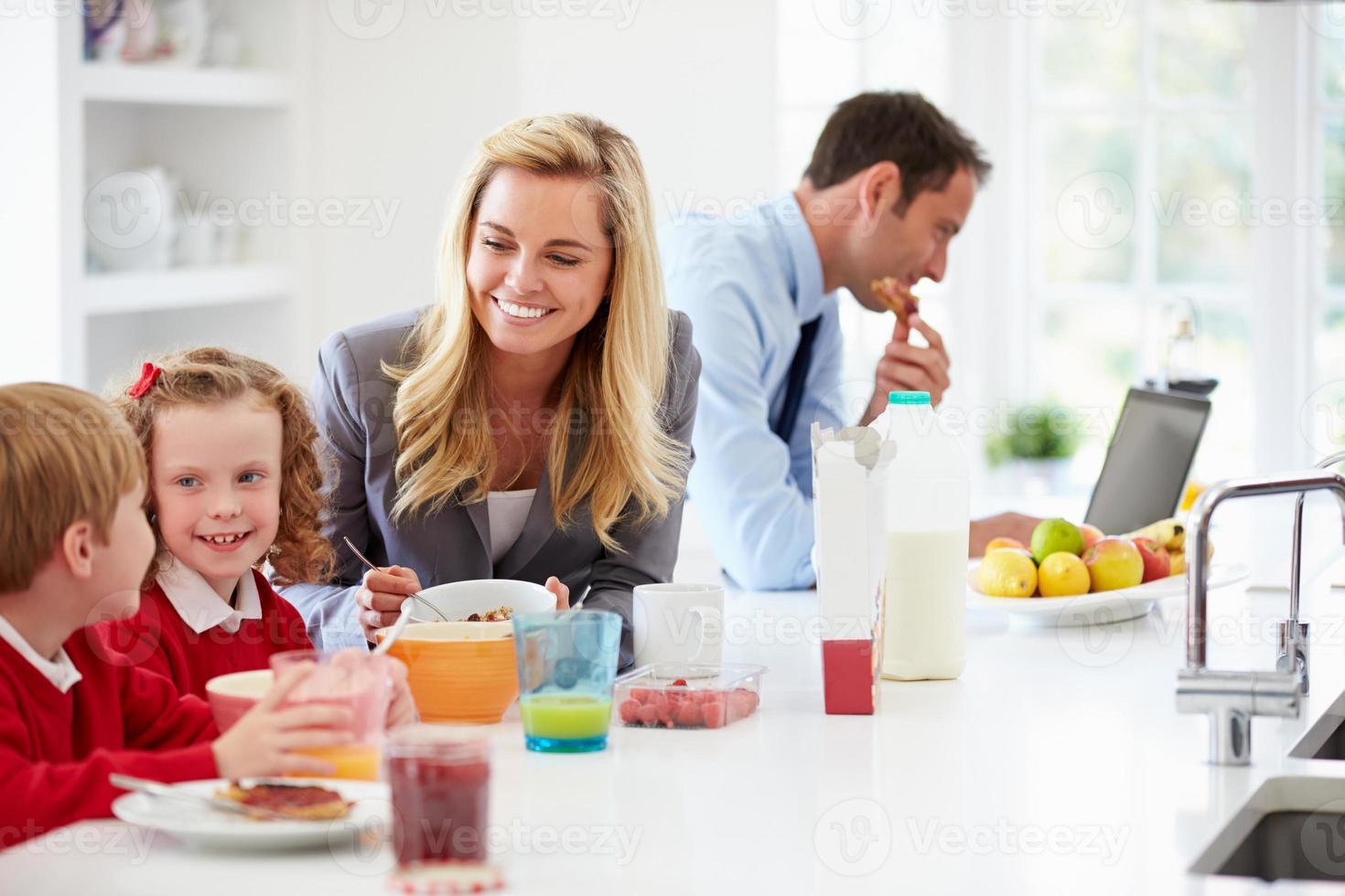 familie ontbijten in de keuken voor school en werk foto