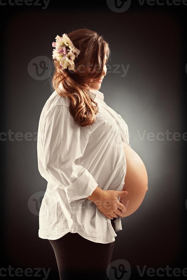 zwangere vrouw die haar buik houdt foto