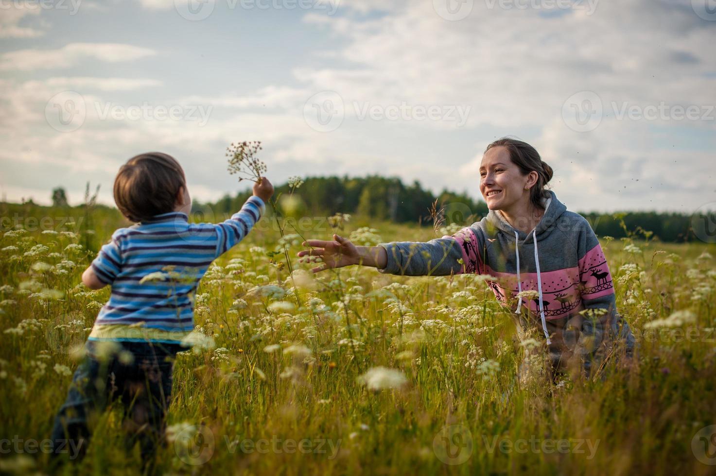 zoon geeft moeder bloemen foto