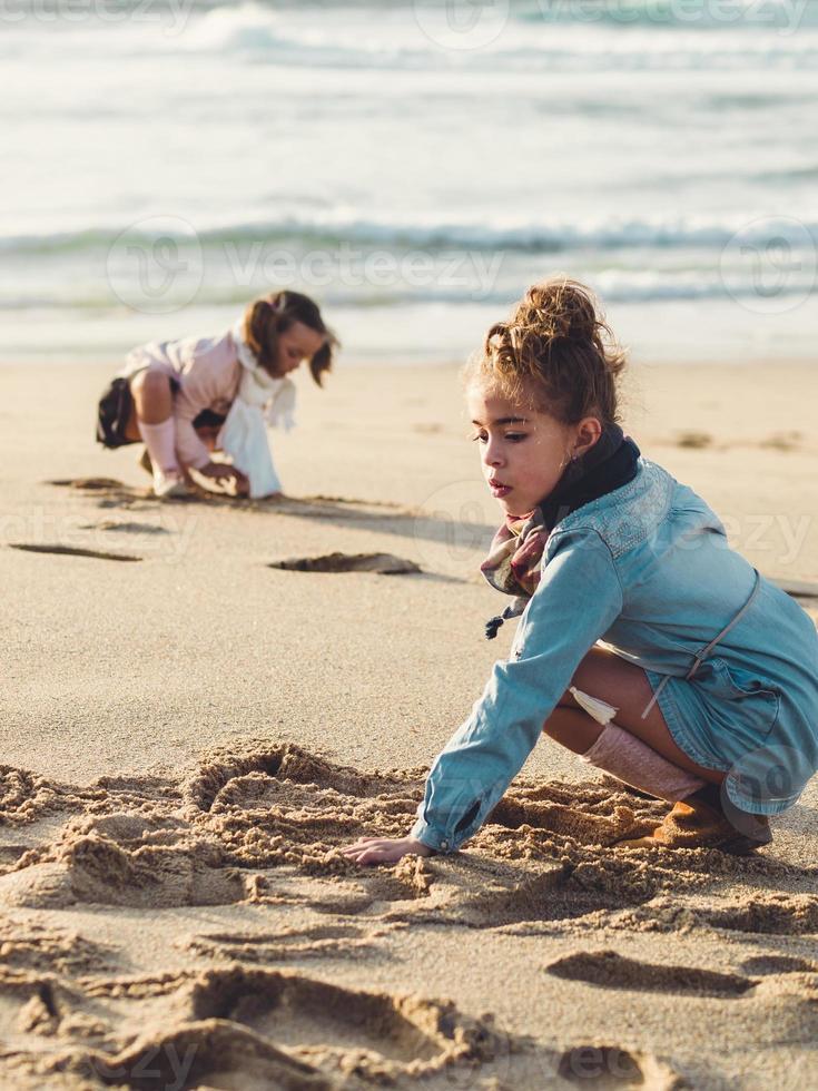 twee kleine meisjes gehurkt en spelen op het strand foto