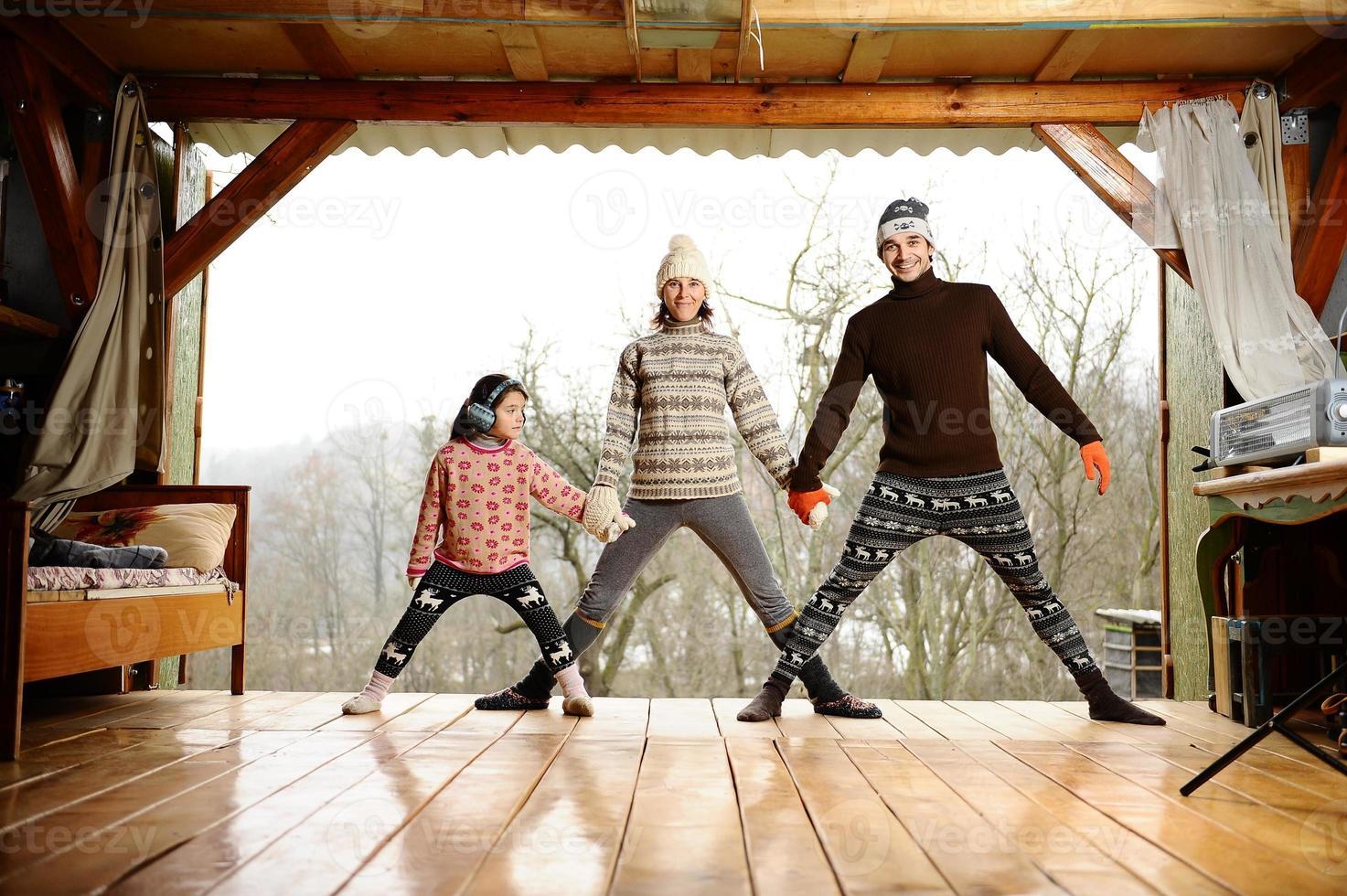 jong gezin op de veranda van een landhuis. foto