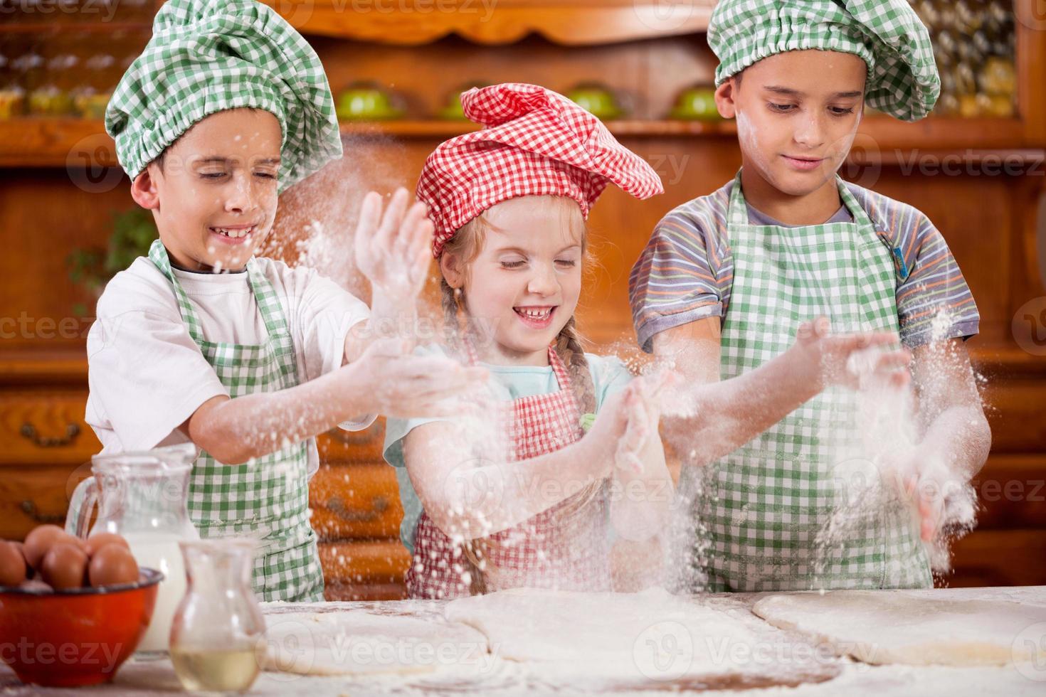 drie grappige jonge kind handen schudden met bloem in de keuken foto