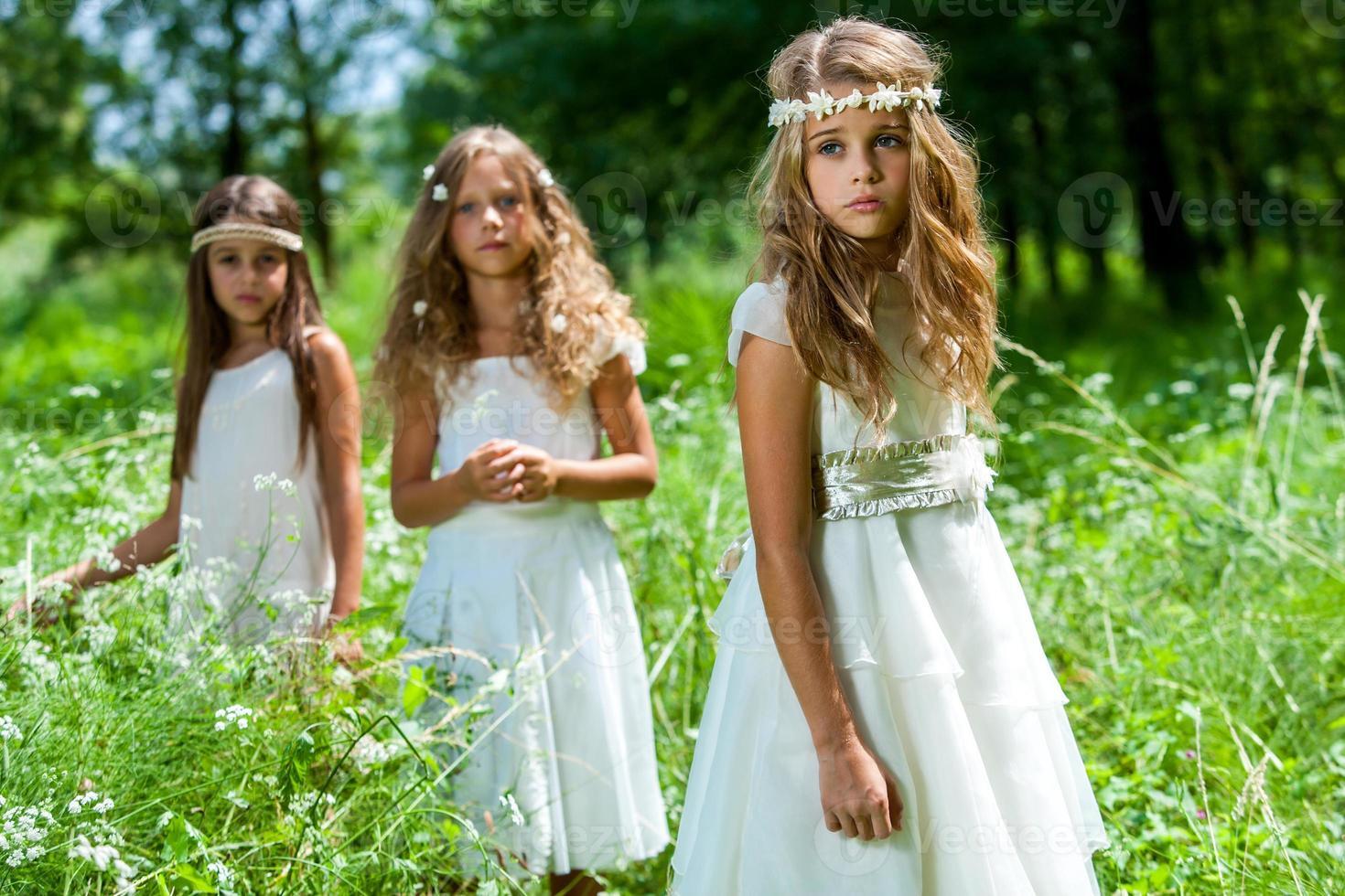 drie meisjes dragen witte jurken in het bos. foto