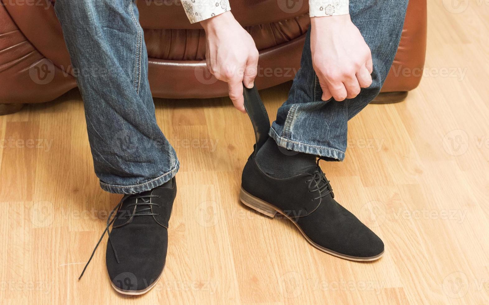 het proces van het dragen van zwarte suède schoenen foto