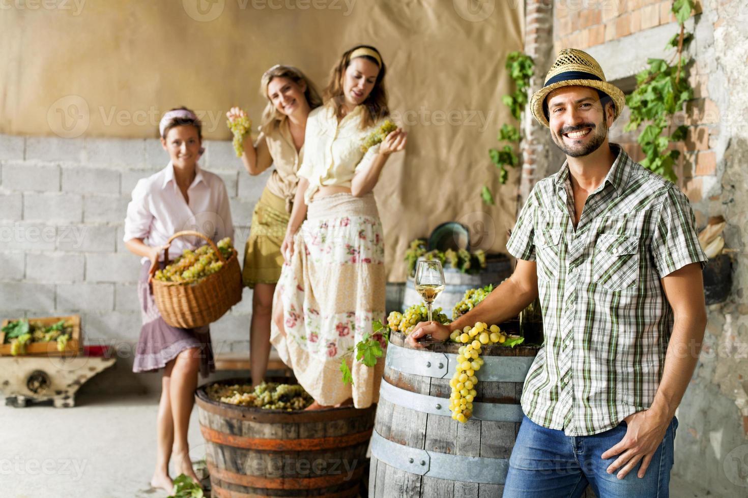 boer drinkt wijn terwijl vrouwen druiven beuken foto