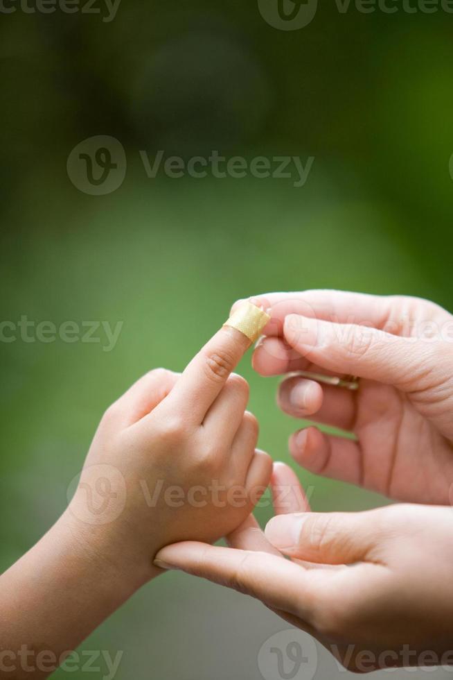een pleister op een gewonde vinger plakken foto