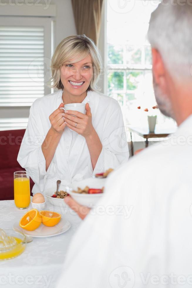 lachende volwassen vrouw ontbijten met bijgesneden man foto