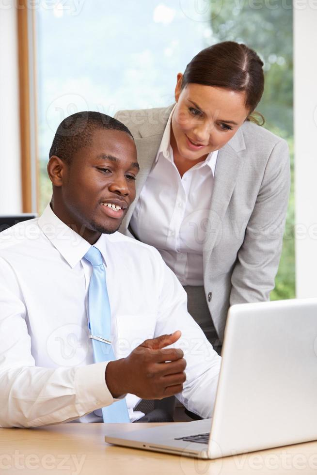 zakenman en zakenvrouw met behulp van laptop op kantoor foto