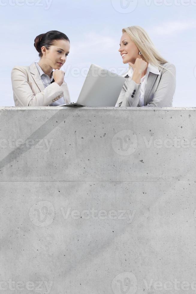 vrouwelijke ondernemers kijken naar laptop terwijl je op terras tegen hemel foto