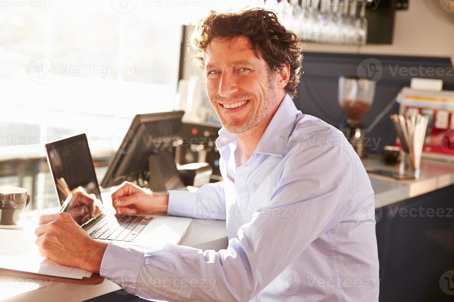 mannelijke restaurantmanager die op laptop werkt foto
