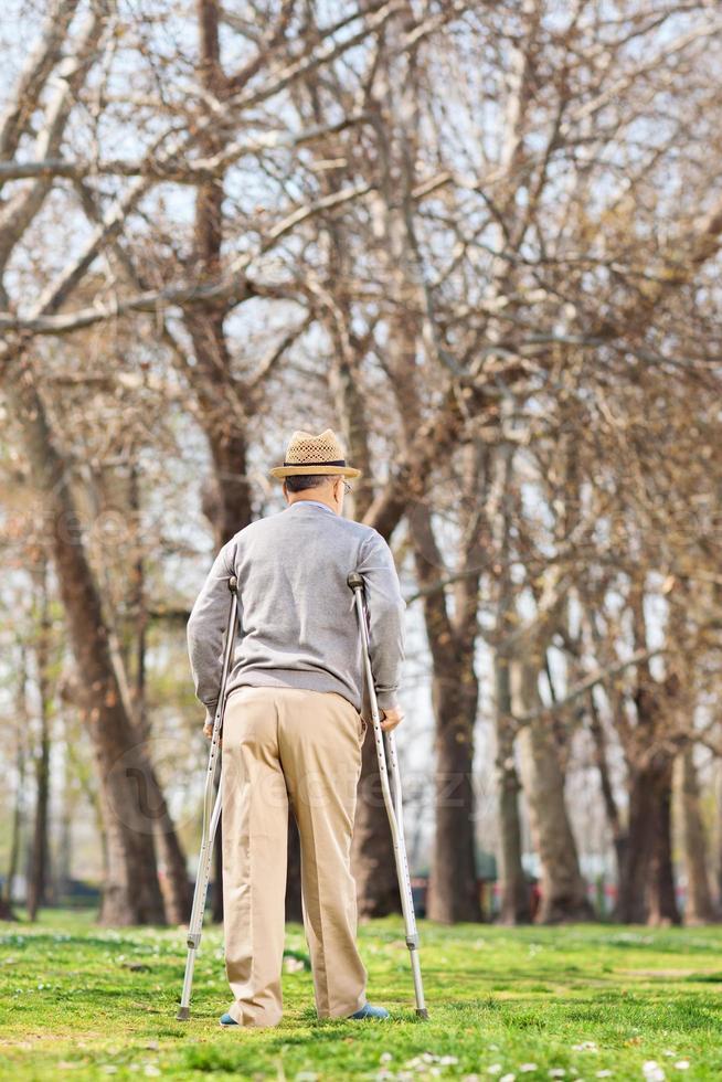 bejaarde man met krukken, wandelen in het park foto