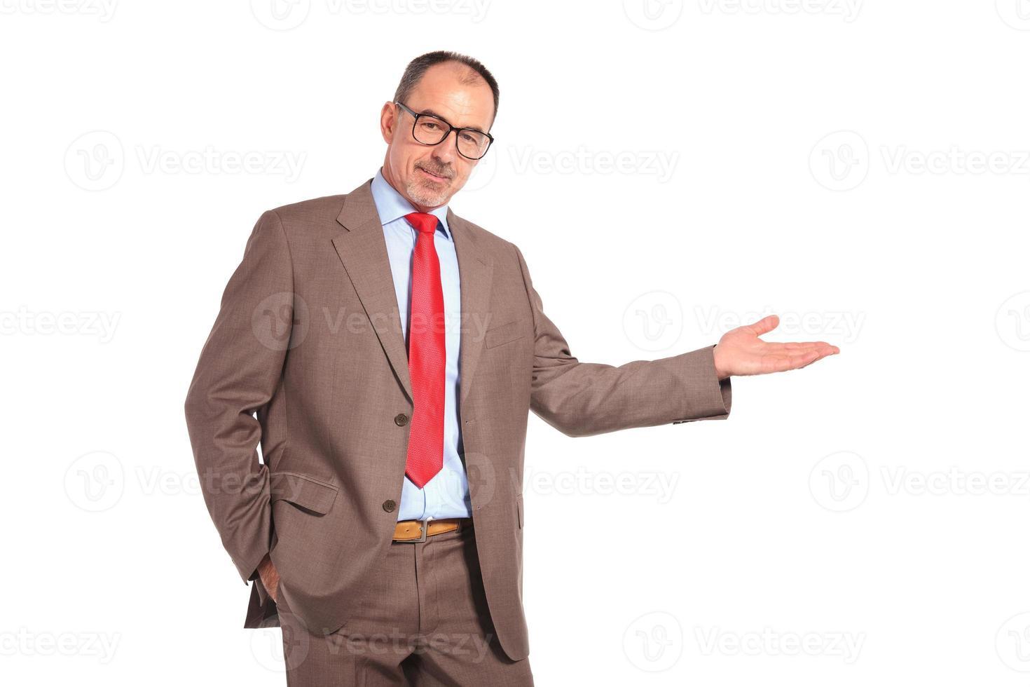 oude zakenman die iets aan zijn zijde presenteert foto