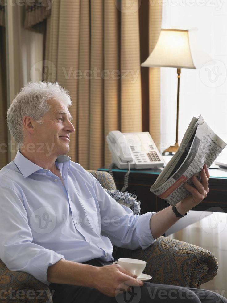 zakenman krant lezen in fauteuil foto