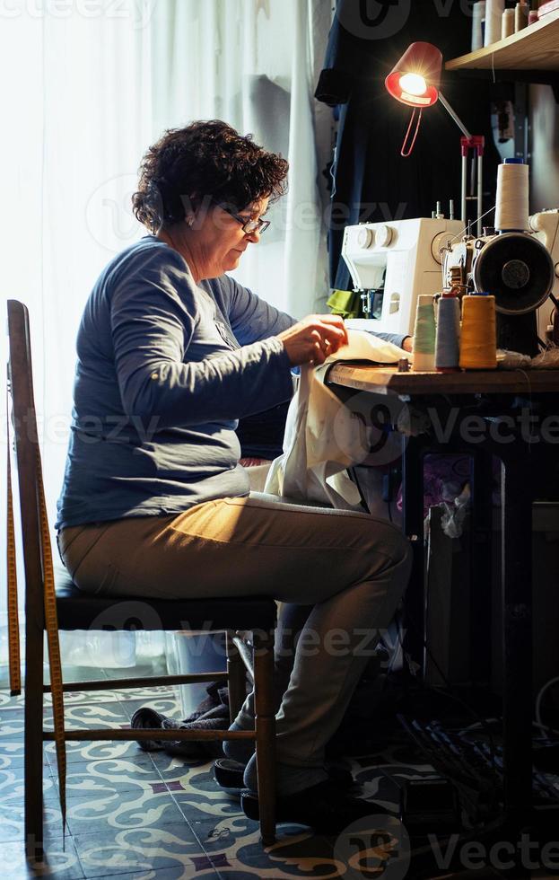 vrouw van middelbare leeftijd naaien foto