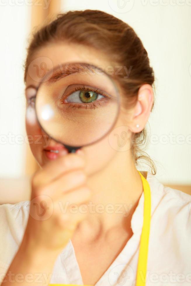 vrouw kijkt door vergrootglas. foto