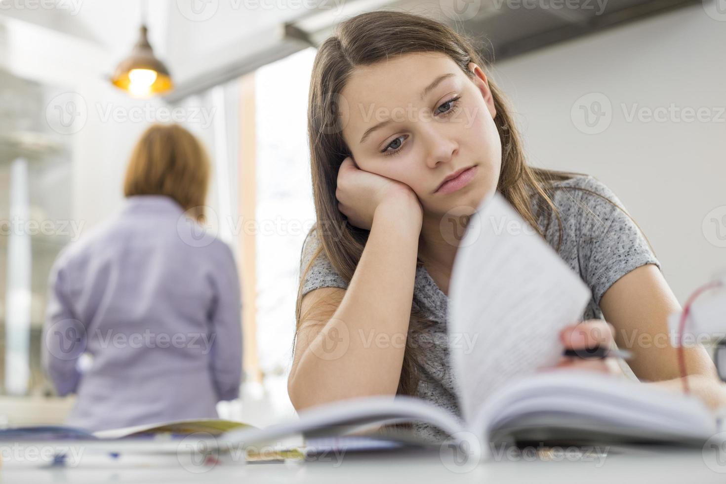 verveeld meisje studeren aan tafel met moeder in de achtergrond staan foto