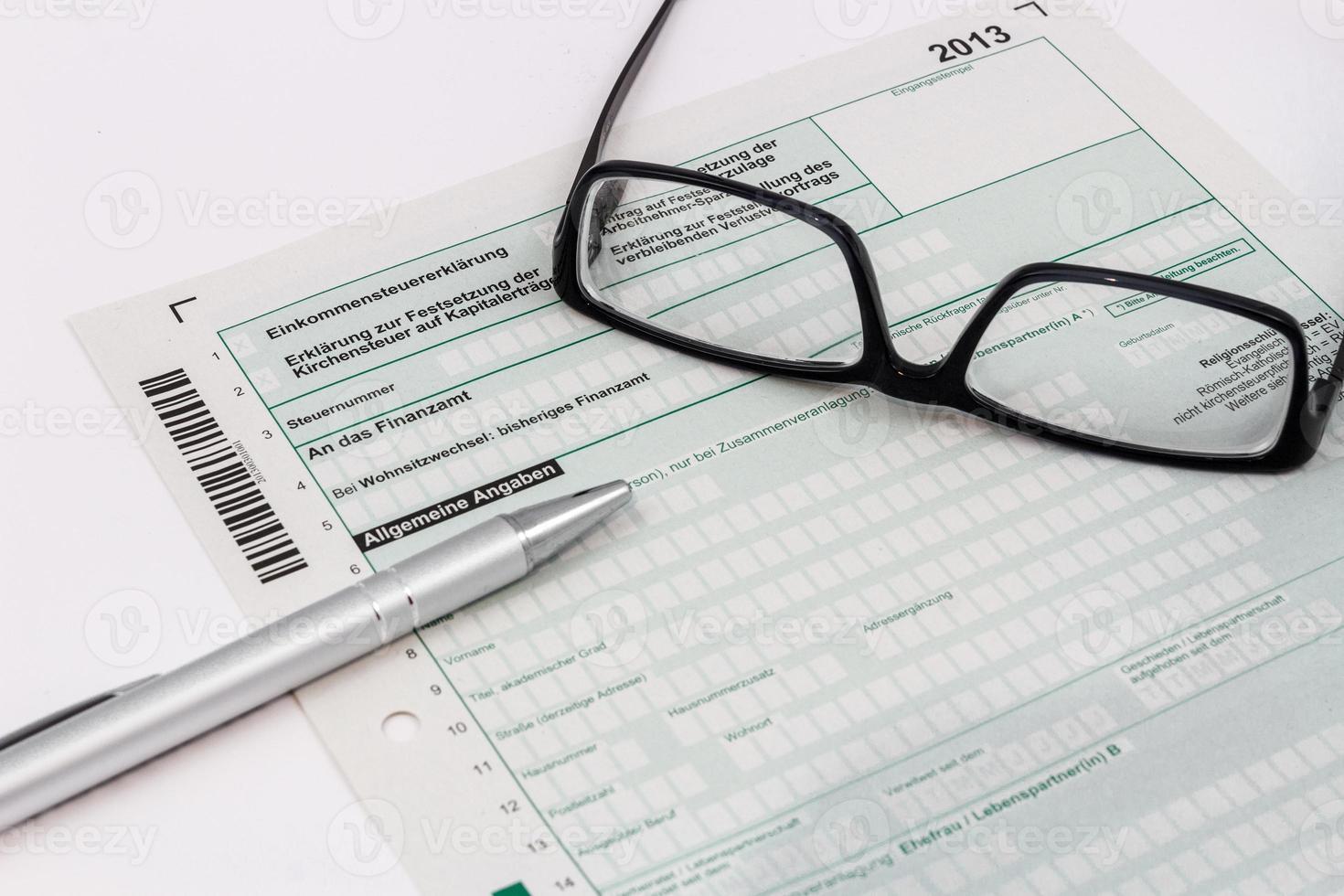 vorm van aangifte inkomstenbelasting met balpen en bril foto