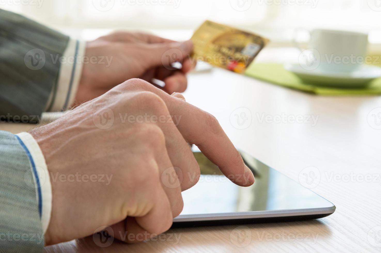 man met creditcard en tablet pc foto