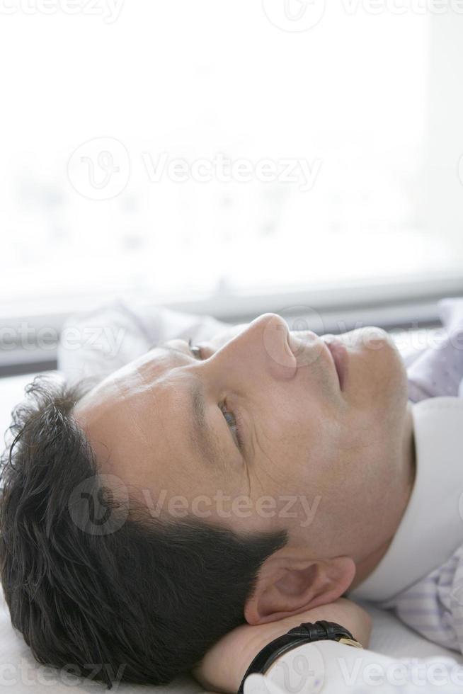 zakenman liggend op bed foto