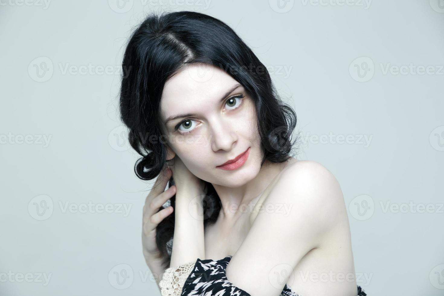 glamoureuze jonge brunette vrouw met mooie huid en natuurlijke make-up foto