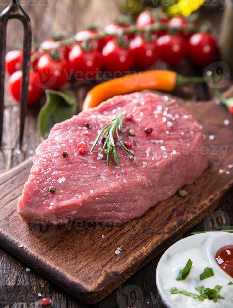 rauwe biefstuk op houten tafel foto