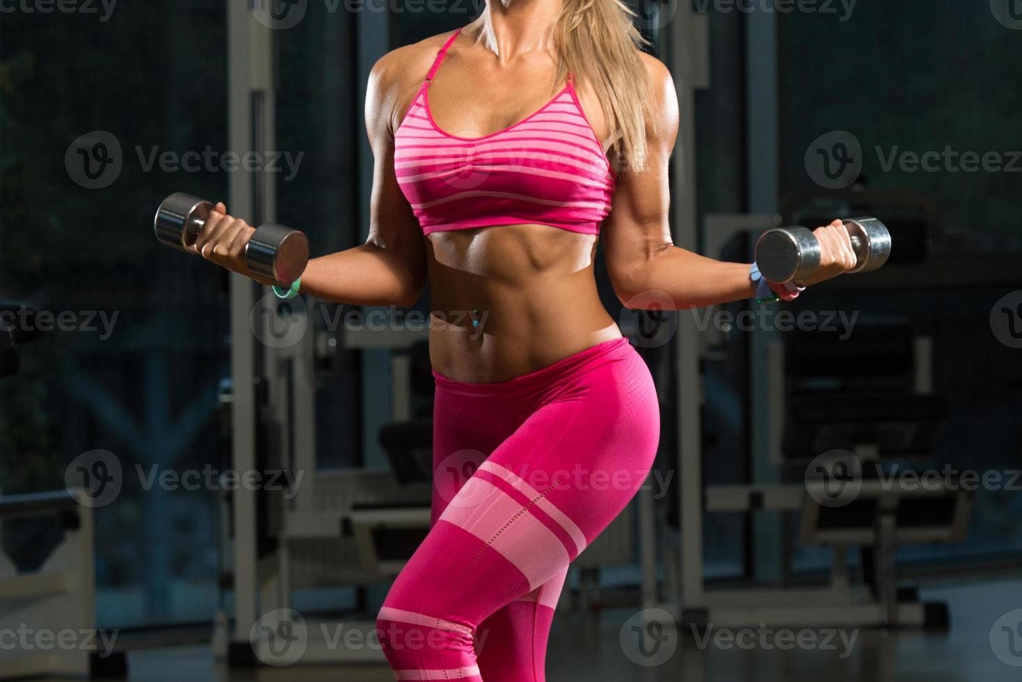 close-up van een vrouw die biceps oefening doet foto
