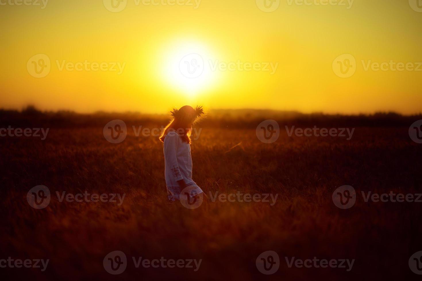 vrouw in een tarweveld bij zonsondergang foto