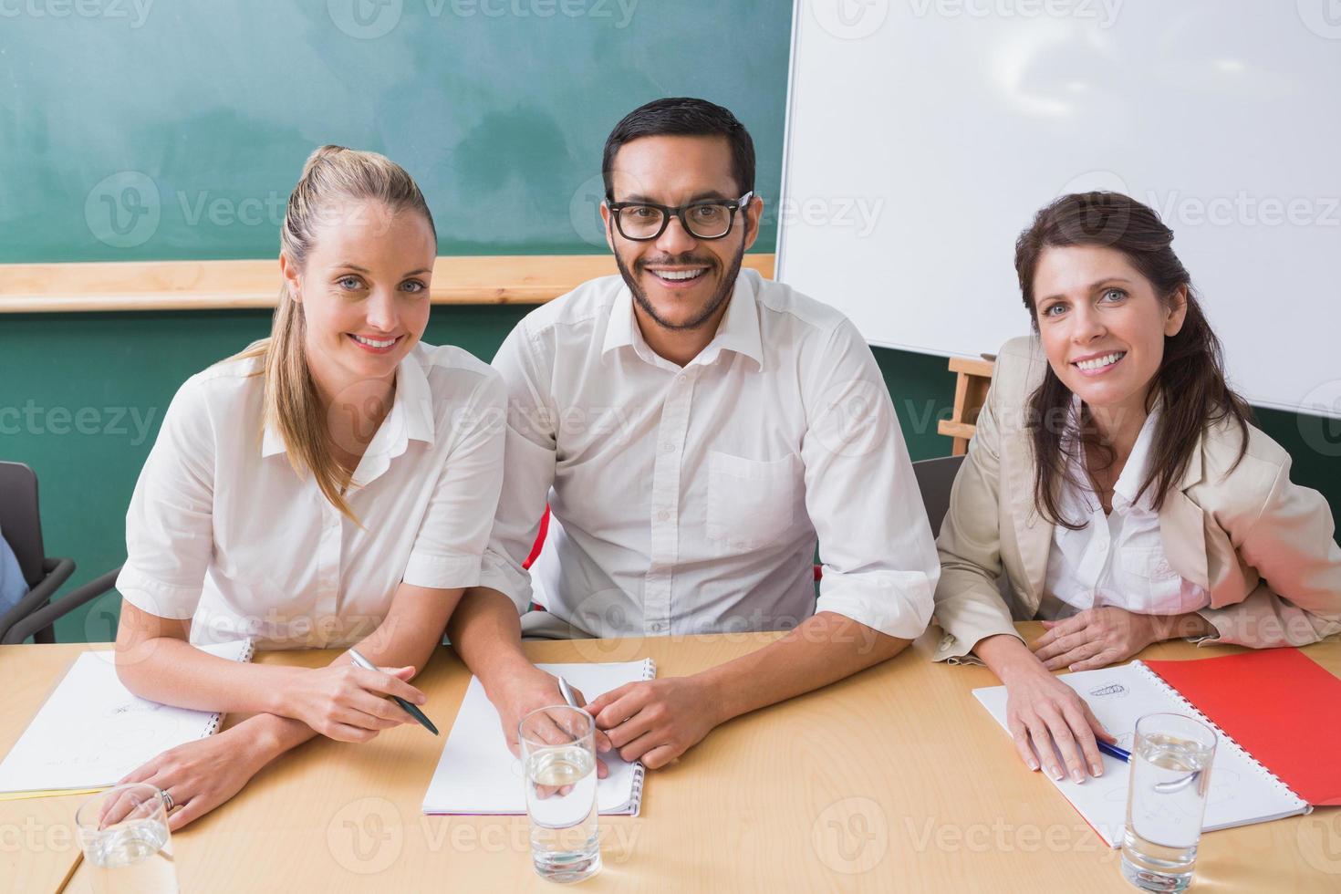 informeel commercieel team dat bij camera tijdens vergadering glimlacht foto