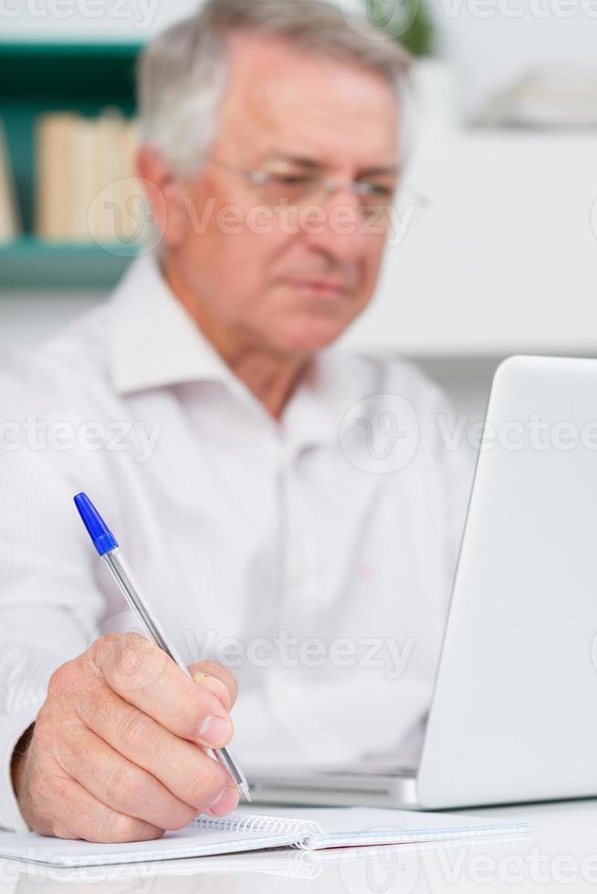 Senior man het maken van aantekeningen met laptop (selectieve focus op vinger) foto