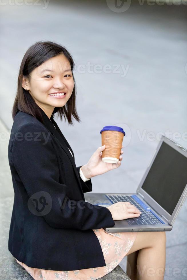 jonge vrouwelijke Aziatische zakenman met behulp van laptop foto