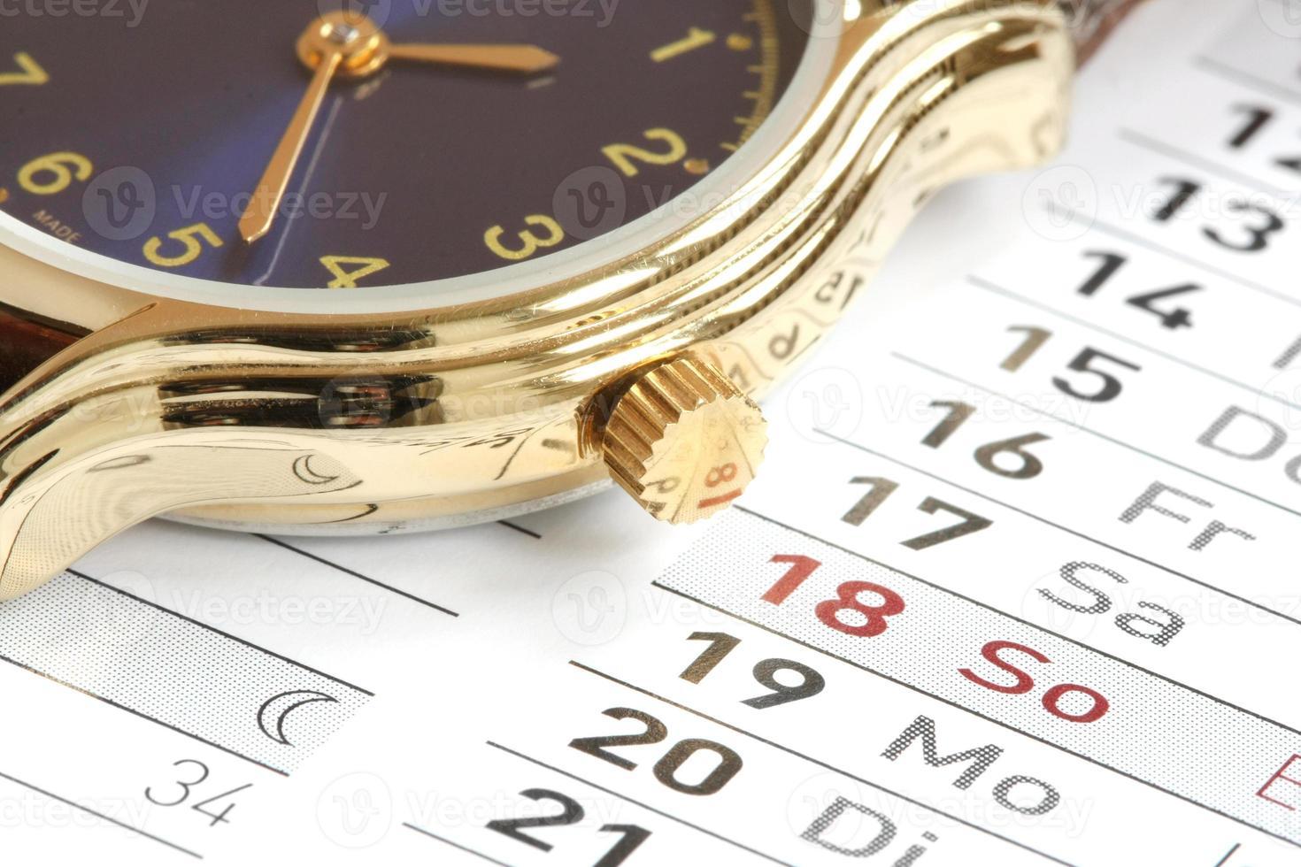 polshorloge op de kalenderachtergrond foto